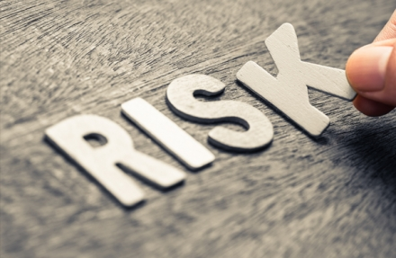 The word risk sitting on a wooden board